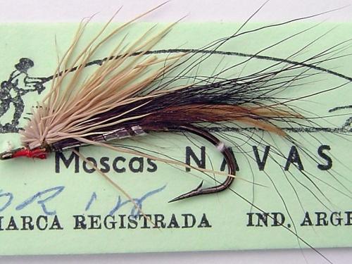 """Una mosca con historia. Creador: José """"Pepe"""" NavasMaterialesAnzuelo: 94840, 9671 o 3366 o Mustad 3906. N° 2 al 10Hilo: 3/0 o 6/0 negro o marrónCuerpo: Tinsel chato plateado (o dorado)Bajo ala: pelo de ternera o chivo de color negro Ala: dos plumas ..."""