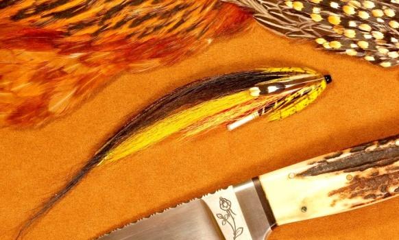 Entre todas las moscas tubo no hay duda de que la Sunray Shadow es una de las más populares y efectivas. Mi primer contacto con esa mosca tubo fue en el Lodge Kau Tapen en Tierra del Fuego. No hacía mucho que habían comenzado las operaciones y el guía principal era Roland Holmberg, un sueco muy conocido que guiaba a pescadores de Atlantic salmón en el renombrado río Gaula, en Noruega. Roland pescaba con cañas de dos manos y moscas tubos, una verdadera novedad para nosotros que hasta ese momento solo empleábamos cañas de una mano. Hace más de treinta y cinco años ver a un pescador pescar una Sunray Shadow a gran velocidad, con una línea de flote y una caña de spey era todo un espectáculo y es que solo los pescadores europeos realmente en esos momentos pescaban asiduamente con cañas de dos manos, en nuestras aguas no existían y en los Estados Unidos todavía no eran muy populares a pesar que pescadores como Mike Maxwell ya eran sinónimo de Spey Casting. Roland me regaló unas Sunray Shadow muy sencillas, un simple  ala de ciervo y cabra atadas sobre un tubo transparente, que mostraban sin lugar a dudas las marcas de los dientes de muchas sea trout. Sin perder demasiado tiempo até copias conservando los originales y desde esos días he usado moscas tubos conjuntamente con mis streamers normales con muy buenos resultados siempre. Hay modelos de streamers muy difíciles de convertir a tubos y hoy los streamers articulados están presentando batalla pero un buen tubo sigue siendo  insustituible para pescar por ejemplo al swing  con la ventaja de que podemos usar una gran variedad de anzuelos para adaptar el tubo a diferentes aguas y tamaños de peces. La Sunray Shadow original fue diseñada y atada por primera vez en los sesenta por un atador profesional llamado Mr. Raymond Brooks que alquiló el río Laerdal en Noruega entre los 60 y los 90. Estaba atada con pelo negro de mono Colobo, (Colobus sp) de una alfombra que le regaló un amigo, luego al atarla comercialmente Ray Brooks c